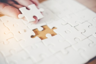 Hand holding piece of blank jigsaw puzzle with paper frame background.