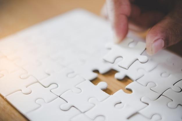 手紙フレームの背景と空白のジグソーパズルの手のひらを保持します。