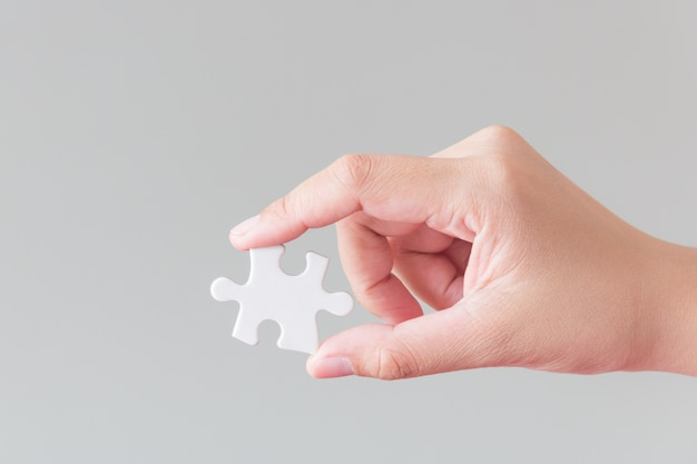 Hand holding a piece of puzzle jigsaw
