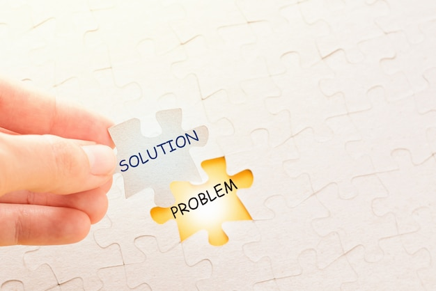 Hand holding piece of puzzle with word solution and putting it on place with problem