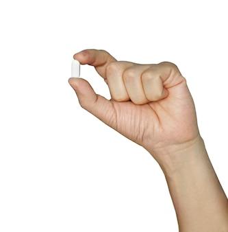 手持ち、白い背景で隔離の親指と人差し指の間にピル。彼の手に白い錠剤。