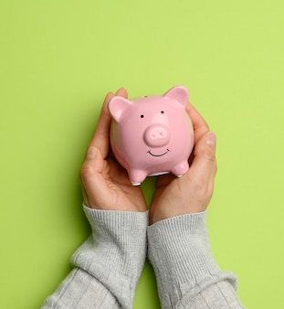 Hand holding pink ceramic piggy bank on a green background, close up