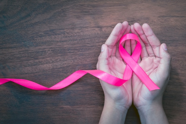 Hand holding pink ribbon on wood.  breast cancer awareness. concept healthcare and medicine