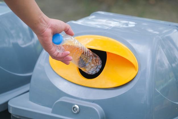 Рука держит пластиковую бутылку и выбрасывает в мусор на переработку. Premium Фотографии