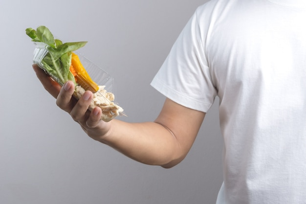Hand holding plastic box of clean food, boiled chicken breasts with vegetables