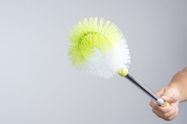 Hand holding plastic cleaner brush with metal stick handle for cleaning flush toilet