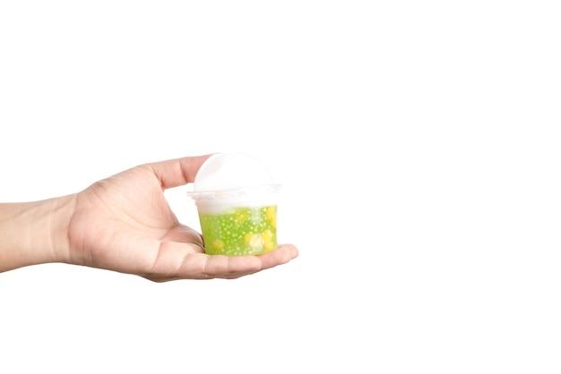 トウモロコシ、ココナッツミルク、サトウのプラスチック製のカップを手に持つ伝統的なタイのデザート