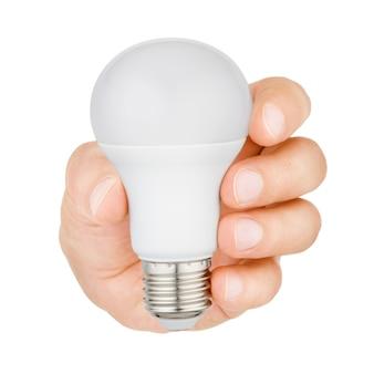 Рука держит пластиковую светодиодную лампочку на белом фоне