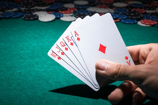 Hand holding playing card on poker table