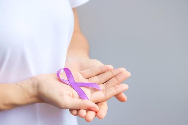 Рука, держащая фиолетовую ленту для рака поджелудочной железы, пищевода, яичек, мира альцгеймера, эпилепсии, волчанки, саркоидоза, фибромиалгии и месяца осведомленности о домашнем насилии. концепция всемирного дня борьбы с раком
