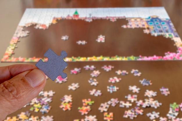 パズルのピースを持っている手、パンデミックのために家にいる期間の活動の概念。