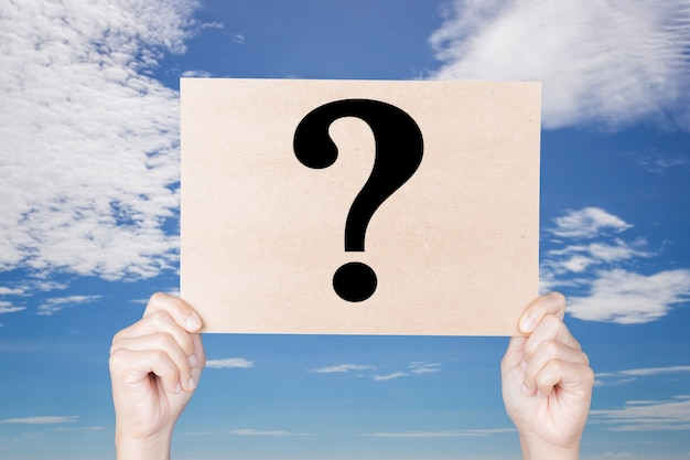 Hand holding question mark sign on blue sky background