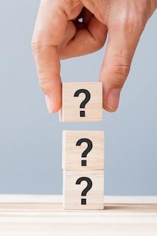 테이블 배경에 있는 나무 큐브 블록에 물음표(?)를 들고 있는 손. 자주 묻는 질문(faq), 답변, q&a, 정보, 커뮤니케이션 및 질문 개념