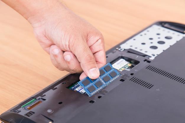 Hand holding ram back side of laptop