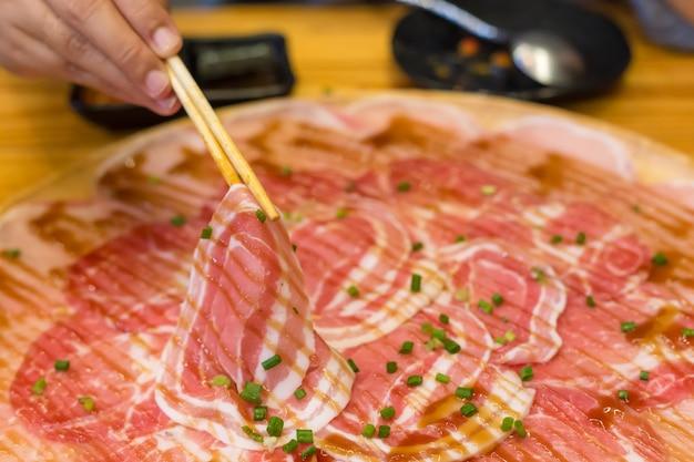 Hand holding raw pork using chopsticks