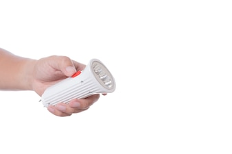 Hand holding rechargeable flashlight with wall charge plug
