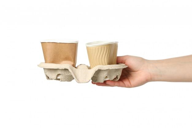 Рука держа бумажные стаканчики рециркуляции, изолированные на белом фоне