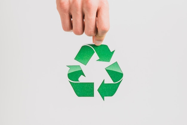 Hand holding recycle symbol on white background