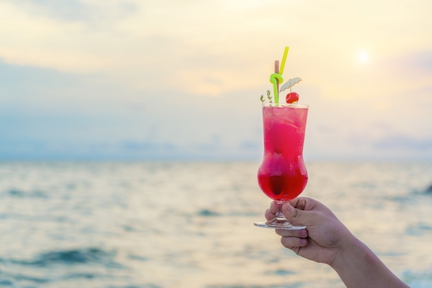 Hand holding red cocktail drink in twilight sea & sky background.