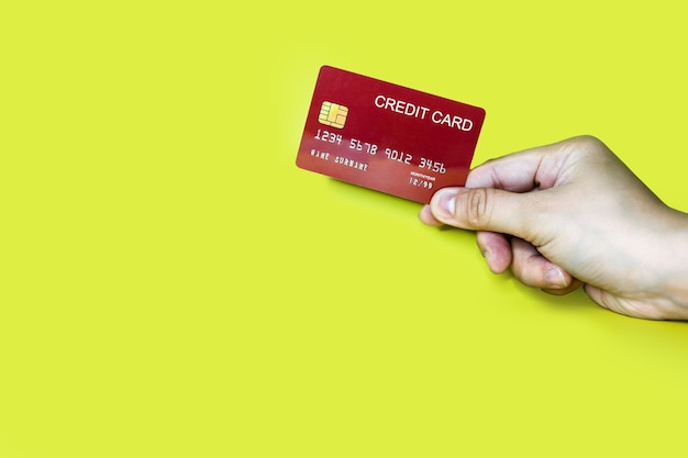 Hand holding a red credit card on a yellow background, credit card can be used to pay for goods or services, credit card concept. credit card clipping path.