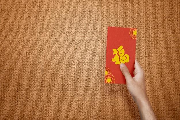 テクスチャード加工の壁が付いた赤い封筒(angpao)を持っている手。旧正月おめでとう