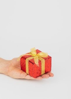 Hand holding red gift box with golden ribbon