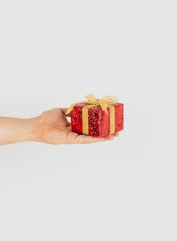 손을 잡고 황금 리본을 가진 빨간 선물 상자