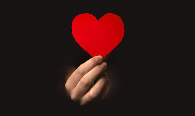 Hand holding red heart on black background. health insurance, organ donor day, charity photo