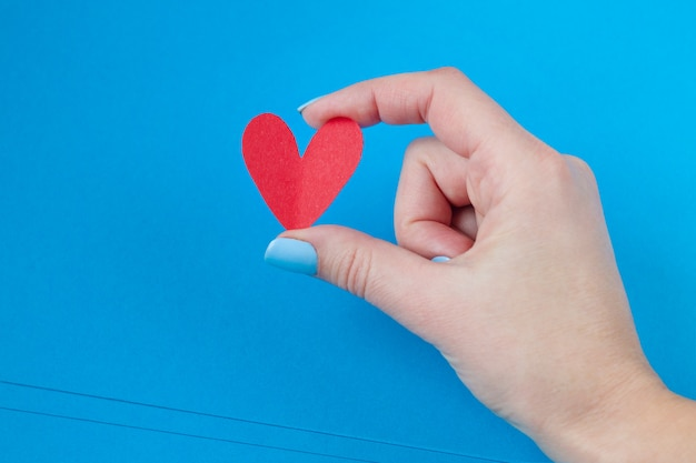 Hand holding a red heart on a blue background. background for valentine's day