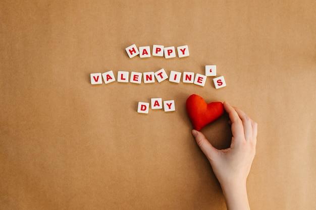 幸せなバレンタインデーのテキストの横に赤いハートを持っている手。