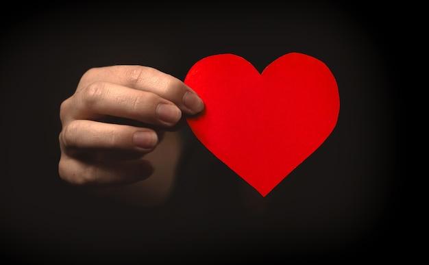 Рука держит красное сердце на черном фоне. любовь от темной концепции. медицинское страхование, день донора органов, благотворительное фото