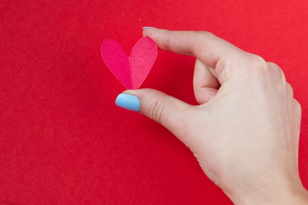 Hand holding a red heart on a red background. background for valentine's day