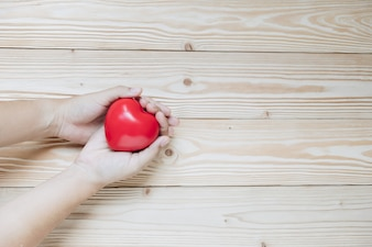 Hand holding red heart shape on wooden background.