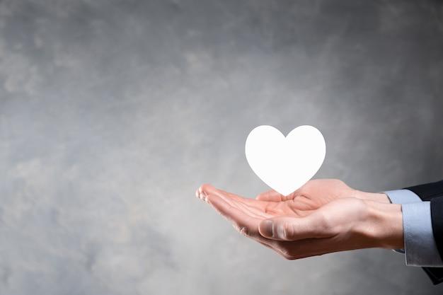 손을 흰색 십자가 기호로 붉은 마음을 잡고. 세계지도 배경입니다. 건강 관리, 건강 보험, 자선 및 의학 개념. 공간을 복사하십시오.