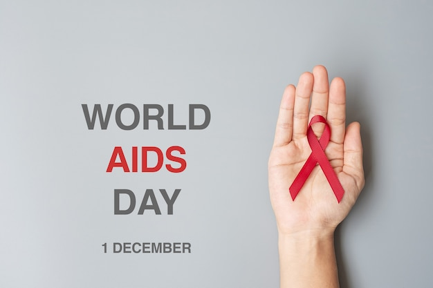 Hand holding red ribbon for world aids day