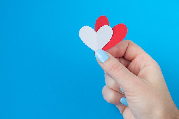 Hand holding a red and white heart on a blue background. background for valentine's day