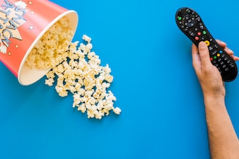 Hand holding remote control next to bucket of popcorn