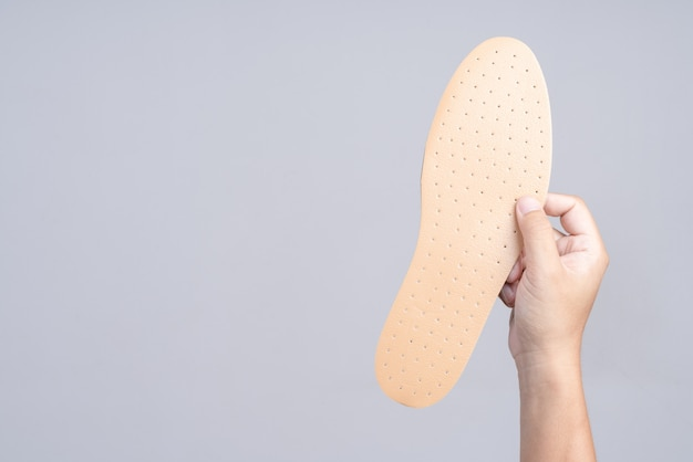 Hand holding replacement shoe sole