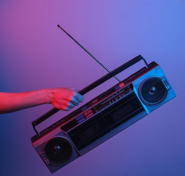 レトロなラジオテープレコーダーを持っている手。青赤ネオングラデーションライトで。ポップカルチャー。 80年代のレトロな波