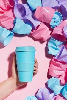 Mano che tiene tazza riutilizzabile accanto a bicchieri di plastica