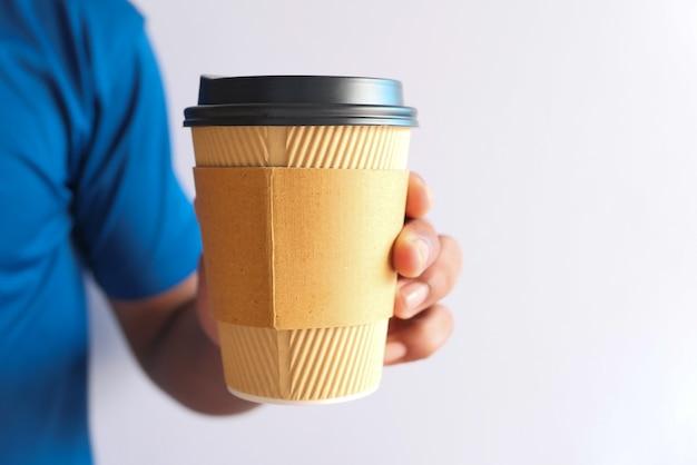 再利用可能なエココーヒーカップを持っている手がクローズアップ。