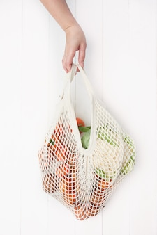 Hand holding a reusable mesh bag filled with fruits and vegetables on white wooden background.