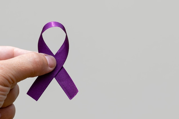 Hand holding ribbon with purple bow.