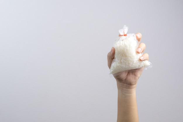 Hand holding rice in plastic bag sealed by rubber band, an ordinary thai food