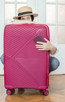 Рука румынский паспорт на розовом фоне чемодана и готовые путешествия.
