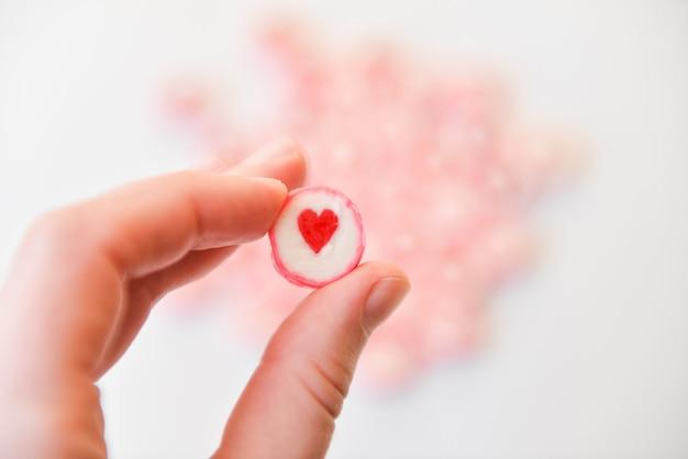 Рука держит круглую конфету с сердцем