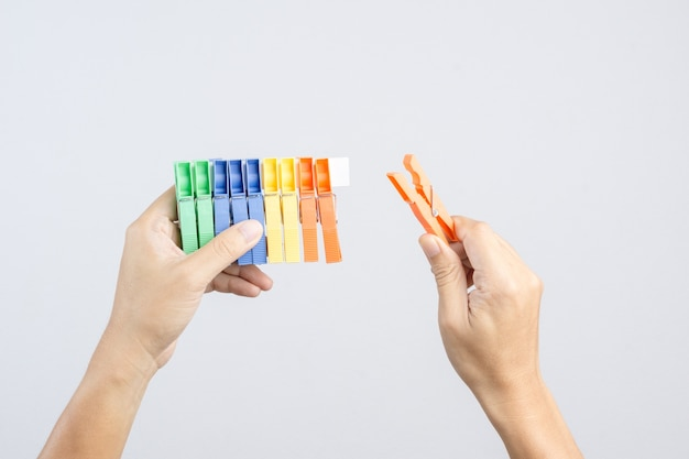 Hand holding row of   colorful plastic cloth clamp or clip