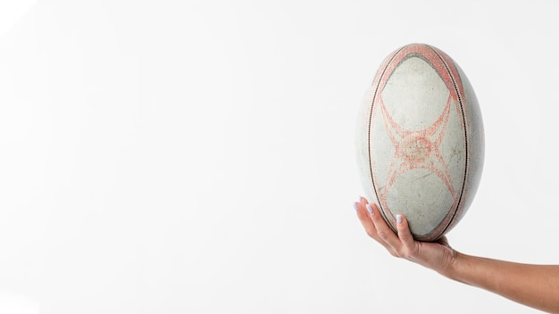 Hand holding rugby ball with copy space
