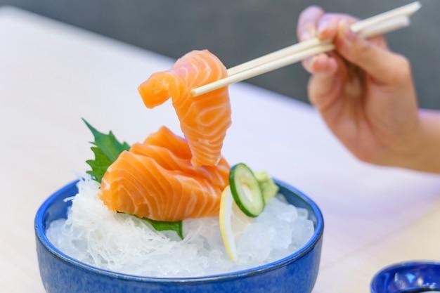 Hand holding salmon sashimi using chopsticks - raw fresh salmon sliced
