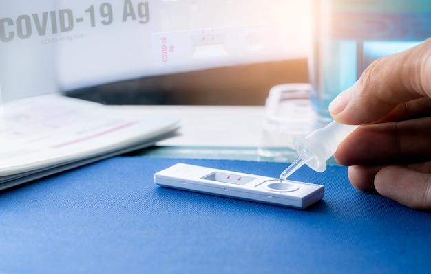 サンプルチューブを手に持って、covid19抗原セルフテストのテストデバイスにドロップします。コロナウイルス感染を検出するための抗原検査キット。迅速抗原検査。コロナウイルスの診断。医療機器。